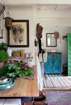 Arbetsbänken i köket har Rolf gjort med hjälp av en flyttbar skiva som ligger på den gamla vedspisen. Blått skåp och gammalt oljetryck från Raja. Husets många trasmattor är köpta på loppis för mellan 10 och 50 kr.