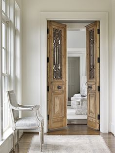 French hallway boasts a light gray French chair placed atop a faded rug in front of carved wood bi fold doors. French hallway boasts a light gray French chair placed atop a faded rug in front of carved wood bi fold doors. The Doors, Wood Doors, Windows And Doors, Salvaged Doors, Sliding Doors, Front Doors, Bi Fold Doors, Screen Doors, Front Entry