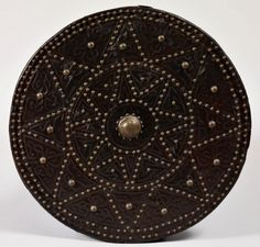"""1692 Scottish Shield (targe) in the Royal Collection, UK - From the curators' comments: """"A Highland targe. The circular wooden shield of different thicknesses of pine, covered on outer side with brown leather, blind-tooled, secured with brass nails. Decorated in four concentric circles outlined with nails. Central brass boss engraved with saltire, zigzag border."""""""