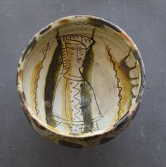 Bowl; earthenware; deep; straight sides and stem with hollow flaring base; decorated with sgraffiato designs, floral motifs round outside and inside a figure in cloak; wavy line near rim; patches and streaks of olive-green and yellow on inside and out; repaired; rim chipped. Culture/periodLate Medieval term detailsLate Byzantine term details Date14thC Production placeMade in: Cyprus