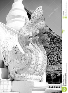 Photo about An incredibly intricate statue of a 5 headed dragon guarding an ancient buddhist stupa in Thailand with a crown and ornate designs. Image of designs, creature, statue - 114458936 Buddhist Stupa, White Dragon, Thailand, Creatures, Stock Photos, Statue, Image, Design, Decor