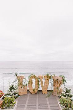 LOVE backdrop for the ceremony, photo by Steve Cowell Photo http://ruffledblog.com/encinitas-beach-wedding #weddingdecor