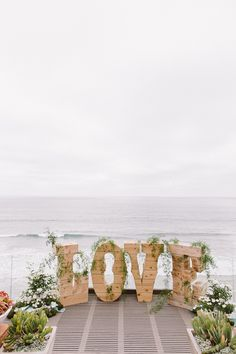 LOVE backdrop for the ceremony, photo by Steve Cowell Photo http://ruffledblog.com/encinitas-beach-wedding #weddingdecor