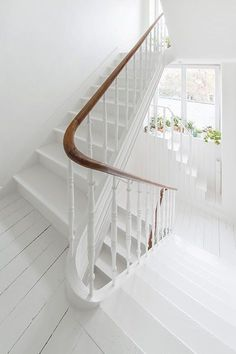 clean white staircase for a shabby chic feel and warm wooden handrail