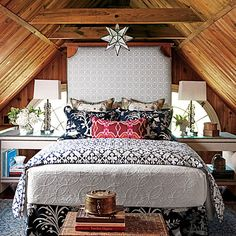 layers of headboards, pillows, and duvet covers...oh my! so pretty and cozy. you'd never get me to leave this room. oh and check those wonderful rafters