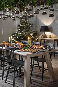 How to create a Winter Wonderland at home | use suspended lanterns over your dining table and fill the space above them with foliage. #christmas #decorate #lighting #magical