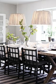 unstained dining table with black painted chairs and white barrel shades  interior design musings