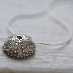It is a heavy little pendant, but just dainty enough. It is 5/8ths of an inch wide and oxidized then polished $65.00