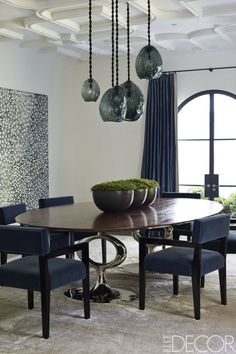 The dining room's chairs, upholstered in a Claremont mohair velvet, are custom made, as is the table by Blackman Cruz; the pendant lights are by David Wiseman, and the painting is by Nick Namarari.