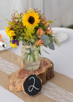 Rustic wedding sunflower centerpiece - sunflowers + wildflowers in mason jars + chalkboard table numbers and wood slices on burlap and lace runners {Sarah Whitmeyer Photography}