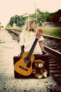 waiting for the train with teddy, guitar and suitcase