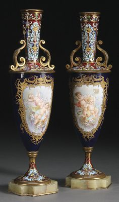 A PAIR OF FRENCH CHAMPLEVÉ AND SEVRES STYLE BRONZE MOUNTED VASES, 19TH CENTURY. The artist painted tapered cylinders depicting cupids within scrolled gilt cartouches below an enameled bronze shoulder and elongated neck, the verso with floral basket sprays. Raised on a champleve enameled gilt bronze spreading foot with shaped onyx plinths.