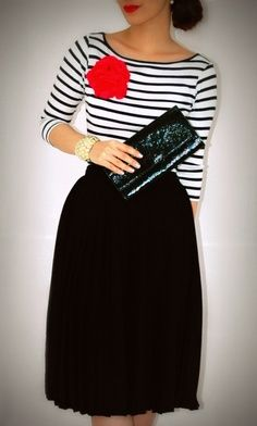 Black skirt, striped top with a red rose brooch and black clutch.