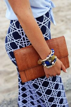 nautical-vibe navy & white pencil skirt + sleeveless blue oxford top knotted at the waist + woven caramel clutch + blue, white, and gold arm party