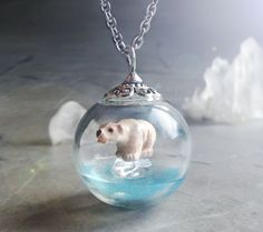 This little glass ball scene necklace features a polar bear on a piece of ice and in the middle of the ocean. Its very cute but also symbolic of the