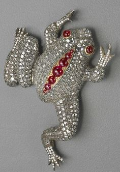 A diamond, ruby, silver and gold frog brooch the body pavé-set throughout with rose-cut diamonds, the feet pavé-set with round brilliant-cut diamonds, accented with round cabochon ruby seven-stone spine and eyes; estimated total diamond weight: 9.00 carats.