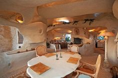"""Dining Room with view of Living Room in """"The Flintstone House"""" built for Dick Clark in Malibu, CA Unique Homes For Sale, Unusual Homes, Flintstone House, Fred Flintstone, Flintstone Cartoon, Caveman Style, Crazy Houses, Weird Houses, Earth Homes"""