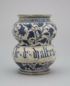 Drug jar of waisted form with everted foot and rim. Buff-coloured earthenware, covered inside and out (but not the rim or base) with presume...
