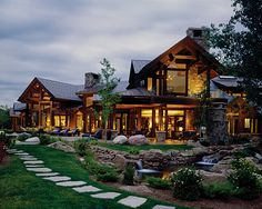 Gorgeous cabin home with stone path, full glass windows, pitched roofs, and lush greens. Im in love.
