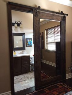 mirrored sliding barn door to master bathroom. mirror on both sides.