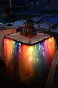 Rainbow Tulle Table Skirt Idea ~ Sew strips of tulle to the back of ribbon and hang over icicle lights around your table. Great idea for any Holiday or Celebration, just change the tulle colors to match the theme!