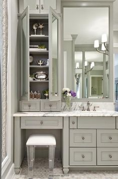 Sophisticated bathroom features gray vanity cabinets paired with a statuary marble countertop. by earnestine