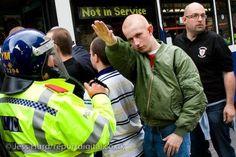 Se les llama skinheads y es una tribu urbana que nace en Inglaterra a finales de los años 60. Muchos de ellos son hooligans del futbol y se caracterizan por su forma de vestir, por llevar la cabeza rapada, por ser violentos y racistas y porque les gusta beber cerveza y vivir al límite. Este personaje forma parte del Edl de Inglaterra y lo intentan detener justo al salir del estadio de Leeds. Algunos de ellos forman parte del fascismo actual o del neonazismo.