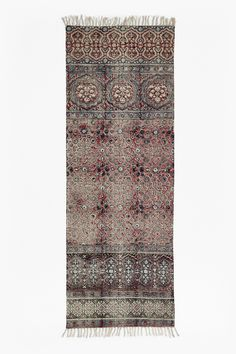 <ul>  <li>  Hand-printed rug with burgundy-hued tile pattern</li>  <li>  Intentionally distressed patches</li>  <li>  Frayed edges</li>  <li>  <strong>75cm x 200cm</strong></li>  </ul>