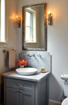 source: Luxe Living Interiors    Amazing powder room design with gray single vanity with carrara marble top and backsplash, polished nickel wall-mount faucet, white porcelain bowl sink and distressed beveled mirror flanked by French sconces.