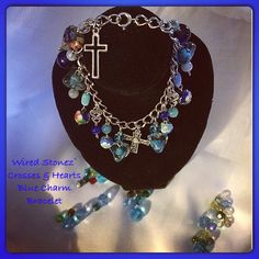 Crosses, hearts, & different glass beads in blue charm bracelet. Silver wire on silver bracelet.