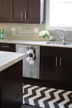 Colors- My kind of kitchen! Like the stainless appliance, dark brown cabinets with touches of green, modern geometric accents and backsplash, and touches of girly and bright white flowers.
