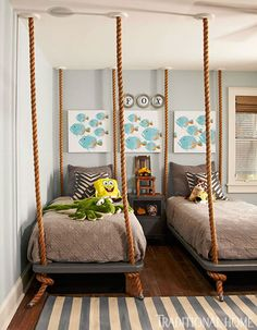 A pair of twin beds appear to hang from the ceiling by thick ropes - Traditional Home® / Photo: Colleen Duffley / Design: Paige Sumblin Schnell & Anna Kay Porch