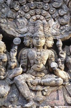 Photograph:A sculpture of the Hindu god Brahma shows him holding a rosary (or scepter), an alms bowl, a bow, and the Rigveda. (Three of Brahma's four faces appear in the photograph.)