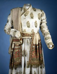 Fine white muslin, embroidered with a regular pattern of floral motifs in blue-black and yellow silk, gold-coloured metal thread and gold-coloured plate (possibly silver-gilt). Neck and front edges, hem edge and wrists are all piped with thin yellow silk. Close-fitting bodice, the extended fronts wrapping right over left, kimono-style. High, v-shaped neckline, with a self-fabric collar band. The front edges of the bodice and the collar band are faced with plain white bias-cut muslin.