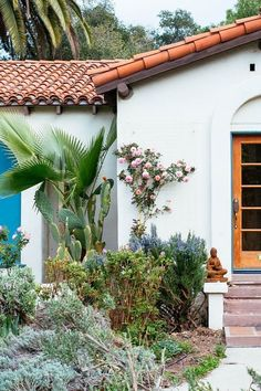 Gorgeous Spanish-style bungalow home with tropical plant landscaping and terracotta tiled roof.