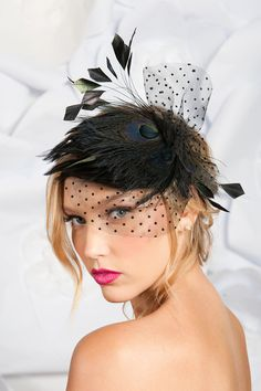 This black cocktail hat is made with feathers, peacock feathers, polka dot veiling and a buckram frame.