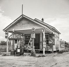 """July Granville County, N. """"Country filling station owned and operated by tobacco farmer."""" Our second look at this establishment offering combustibles and comestibles. Medium format negative by Dorothea Lange. Old General Stores, Old Country Stores, Old Gas Pumps, Vintage Gas Pumps, Route 66, Old Photos, Vintage Photos, Vintage Photographs, Vintage Signs"""