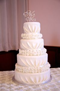 4-Tiered draped and rosette, ivory wedding cake.