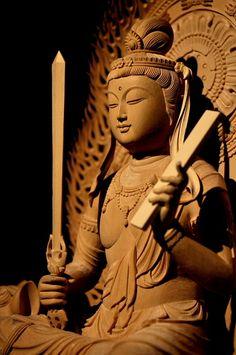 仏像彫刻原田謹刻 文殊菩薩像(もんじゅぼさつぞう) 【文殊菩薩】 文殊は梵名Mañjuśrī(マンジュシュリー)の音写、文殊師利(もんじゅしゅり)の略称である。 智慧をつかさどる菩薩。普賢菩薩とともに諸菩薩の上位に位置し釈迦に侍す。一般に右手に剣、左手に経巻をもち、獅子に乗る姿であらわされる。卯年の守り本尊。 【三人寄れば文殊の智恵】 文殊菩薩の徳性は悟りへ到る重要な要素、般若(智慧)であるが、本来悟りへ到るための智慧という側面の延長線上として、一般的な知恵(頭の良さや知識が優れること)の象徴ともなり、これが後に「三人寄れば文殊の智恵」ということわざを生むことになった。 【般若】 サンスクリット語のprajñā(プラジュニャー)パーリ語paññā(パンニャーの音写語。慧(え)と漢訳される。『悟りを得るための真実の智慧』あるいは、『あらゆるものごとを見通す見識』を意図している。 Buddha Canvas, Buddha Art, Mahatma Buddha, Stone Buddha Statue, Theravada Buddhism, Hindu Statues, Buddha Sculpture, Buddha Painting, China Art