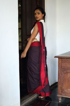 This saree is a tribute to the fiery women writers and freedom fighters of Kerala. Strong, bold and classic. This soot black saree has tiny red checks and a ...