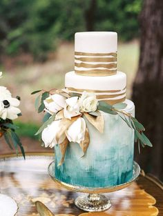 We are obsessed with this gold and blue, watercolor-inspired, fresh floral wedding cake!