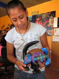Young artist showing off the alebrije she painted.