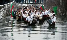 """Men perform the traditional Bulgarian """"Horo"""" dance in the icy winter waters of the river Tundzha in the town of Kalofer, Bulgaria some 200 km east of the capital Sofia, during the Epiphany Day celebrations"""