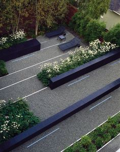 Andrea Cochran Perry Residence, San Francisco  Black concrete walls, strips of stainless steel, and bands of planting material slide past one another, creating a maze like space.  photography: Marion Brenner, Ryan Hughes
