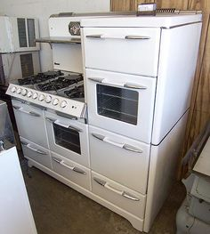 56 inch O'Keefe & Merritt Town and Country (C. 1950), 6 burner double oven, 2 ovens, 2 broilers, storage drawers and bread warmer.