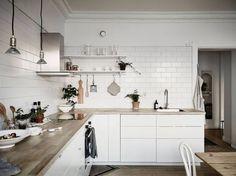 Cocina nórdica con baldosa metro y encimera de madera
