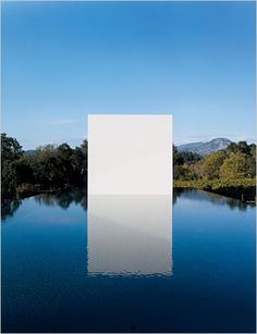 The contrast between the white space and the landscape is complemented by the reflection of the pool. It almost looks like a door...