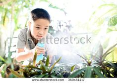 Young Thai boy spray water to the plant in his garden at home. Earth day concept.