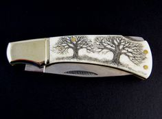 """Twin Oaks"" scrimshaw  pocket knifeDetailed scrimshaw trees hand engraved on a  Rough Rider lockback folding pocket knife."