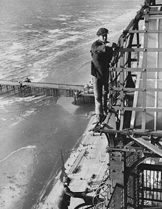 Blackpool illuminations: 1935: Workers fix lamps on Blackpool Tower... Health and Safety!